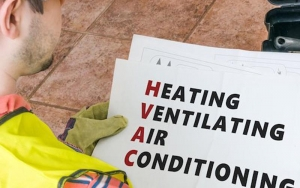 Image of a man holding a HVAC sign