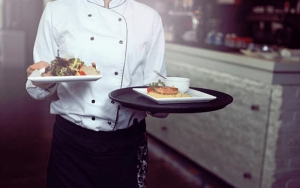 Image of a chef carrying plates of food