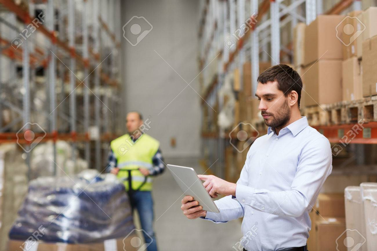 Image of businessman with tablet pc at warehouse