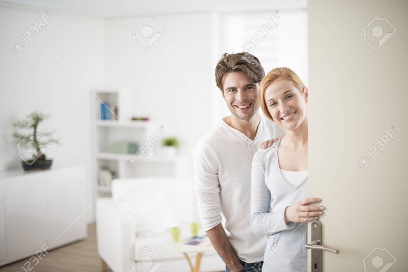Image of Cheerful couple inviting people to enter in home