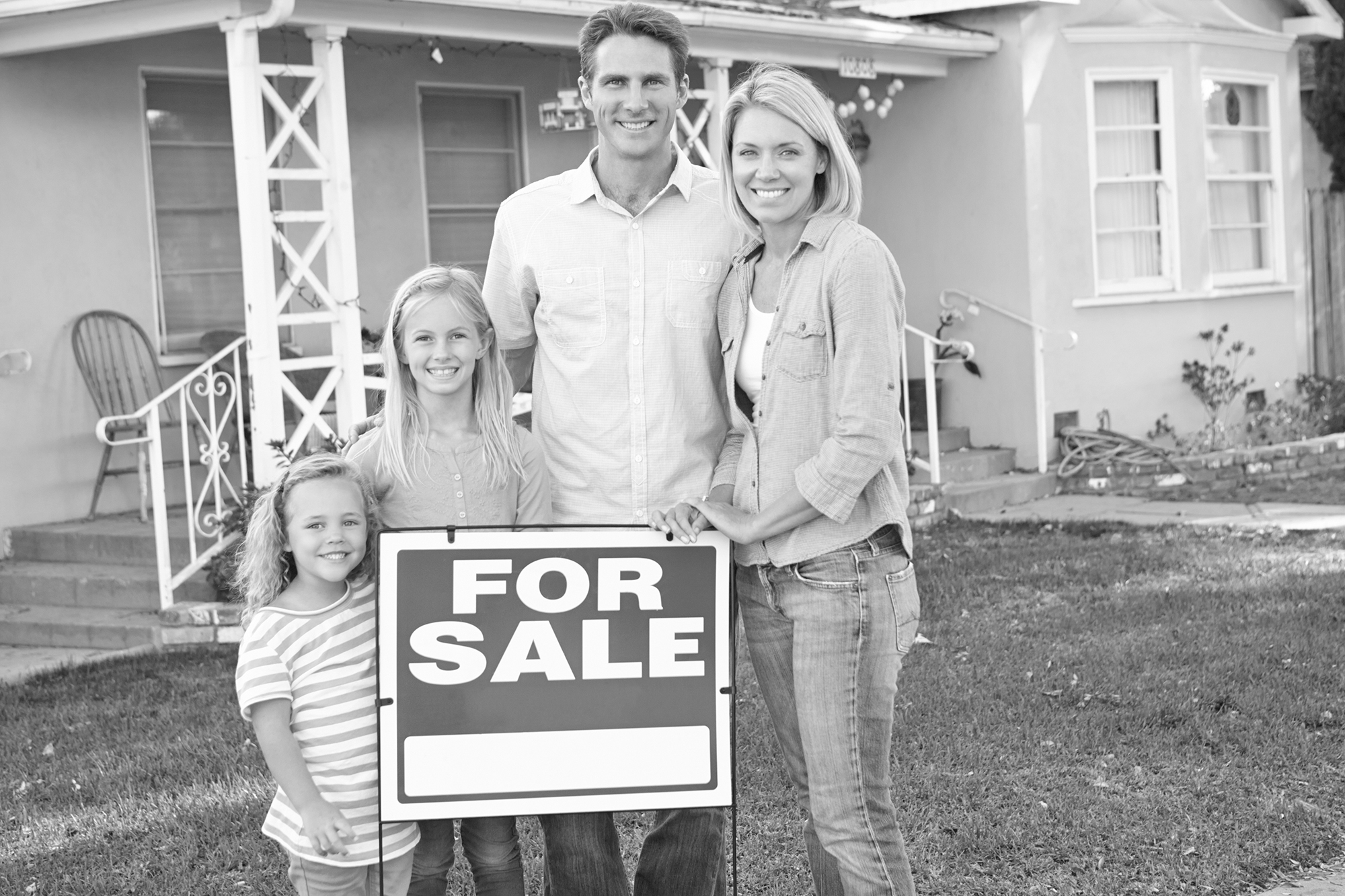 Image of family standing by for sale sign outside home